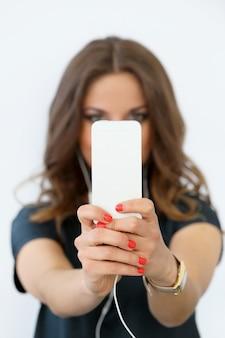 Krullend meisje met mobiele telefoon