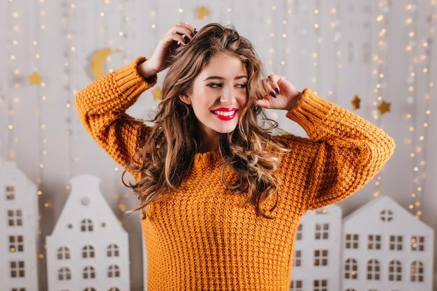 Krullend meisje met rode lippen in oranje sweaterglimlachen
