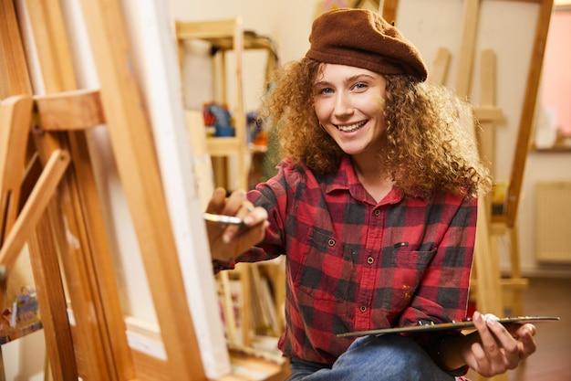 Krullend meisje met schattige glimlach tekent een schilderij