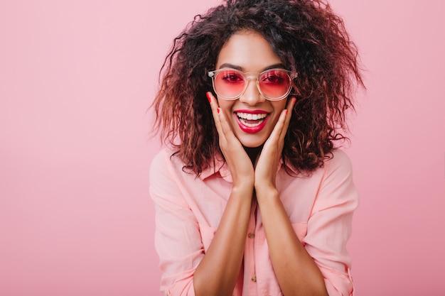 Krullend meisje vangen in trendy zonnebril, koelen en lachen. schattige donkerharige vrouw in roze katoenen kleding poseren met verbaasd gezicht.