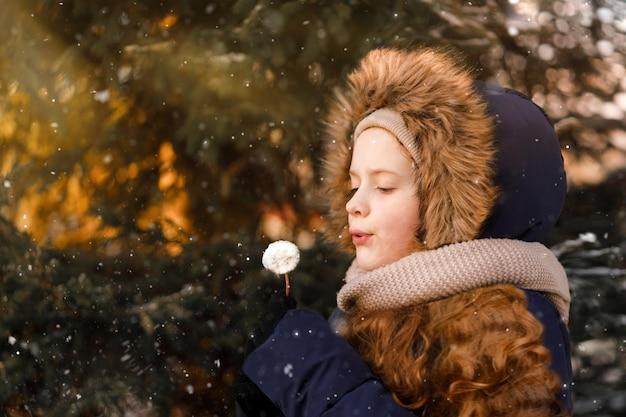 Krullend meisje waait paardebloem in de winterdag. eerste sneeuw.