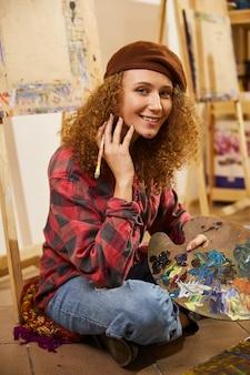 Krullend meisje zit op een vloer, glimlachend en tekent een schilderij