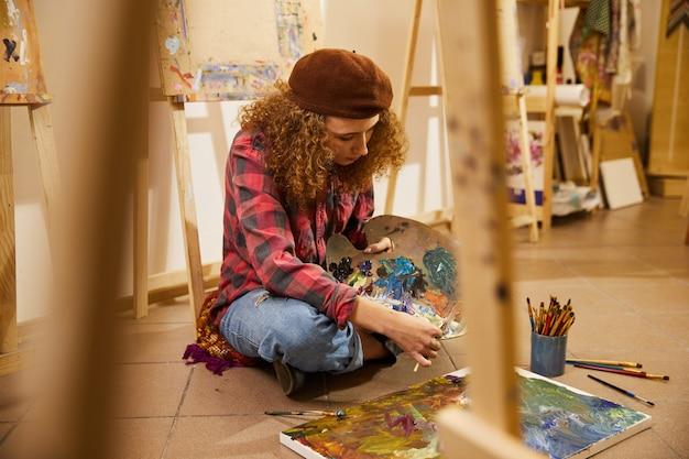 Krullend meisje zit op een vloer, olie mengen en tekent een schilderij