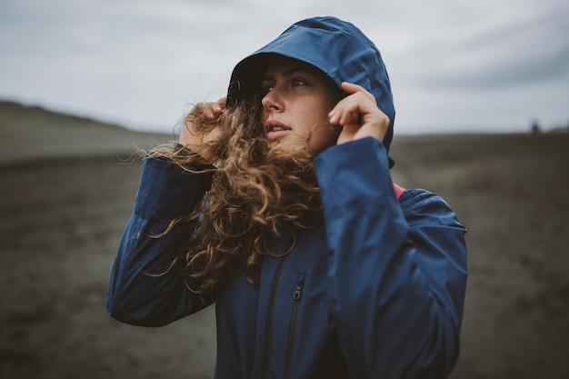 Krullend model dat op het strand staat en geniet van de koude herfstdag met een capuchon over haar hoofd