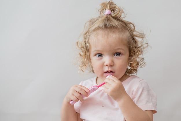 Krullend mooi babymeisje met tandenborstel op grijze muur