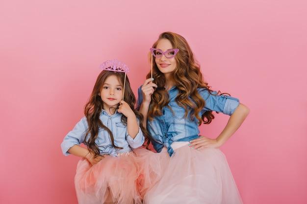 Krullend mooi meisje met paarse kroon poseren naast jonge aantrekkelijke moeder maskerade masker op roze achtergrond te houden. schattige vrouw in vintage outfit met plezier met dochter op verjaardagsfeestje.