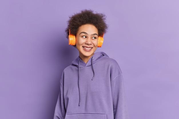 Krullend mooi tienermeisje draagt stereo koptelefoon luistert audiotrack kijkt gelukkig opzij gekleed in sweatshirt.