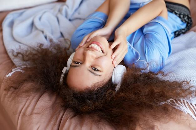 Krullend mulatmeisje dat op het bed ligt met haar hoofd naar beneden, luistert naar favoriete liedje in de koptelefoon, breed glimlachend en raakt de wangen aan, ziet er vrolijk uit.