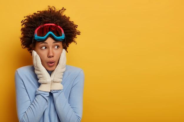 Krullend onder de indruk meisje houdt de handen op de wangen, kijkt verrassend opzij, gekleed in een comfortabele blauwe trui