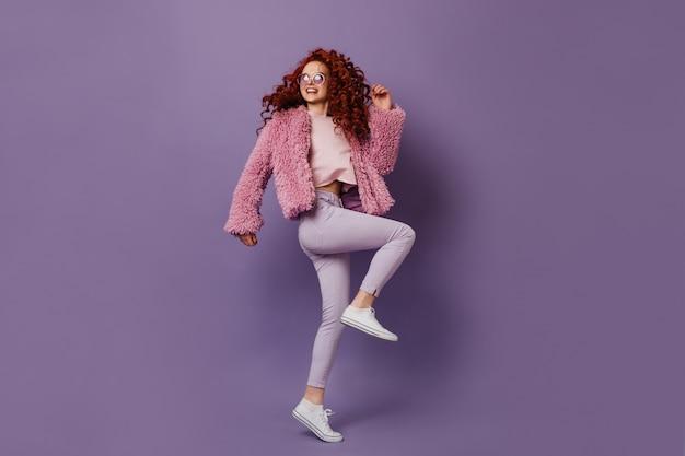 Krullend roodharig meisje in witte sneakers en broek danst en lacht op paarse ruimte.