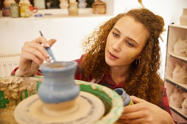 Krullend roodharig meisje is gefocust op het bedekken van een aardewerk vaas voor het bakken