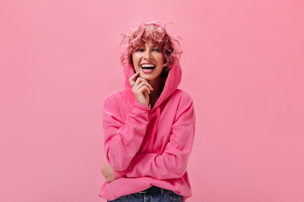Krullend roze-haired vrouw in goed humeur poses op geïsoleerde muur