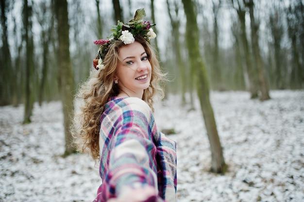Krullend schattig blondemeisje met kroon in geruite plaid bij sneeuwbos in de winterdag.