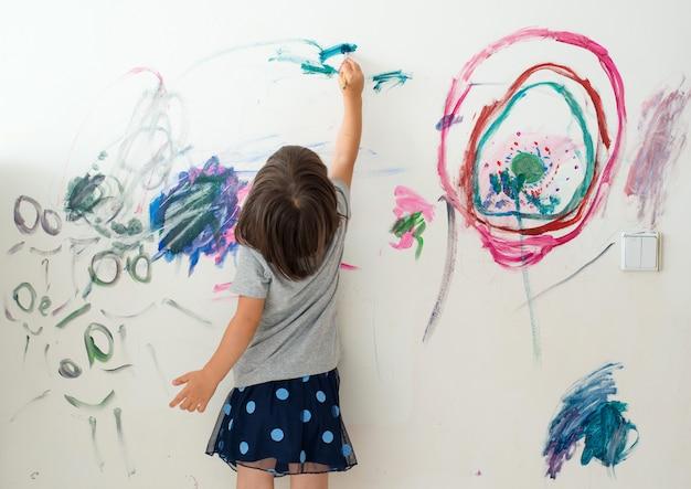 Krullend schattig klein peutermeisje schilderen met verf kleur en penseel muur.