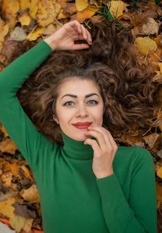 Krullend schattig meisje met open ogen liggen in de herfstbladeren, hand in de buurt van gezicht en glimlach