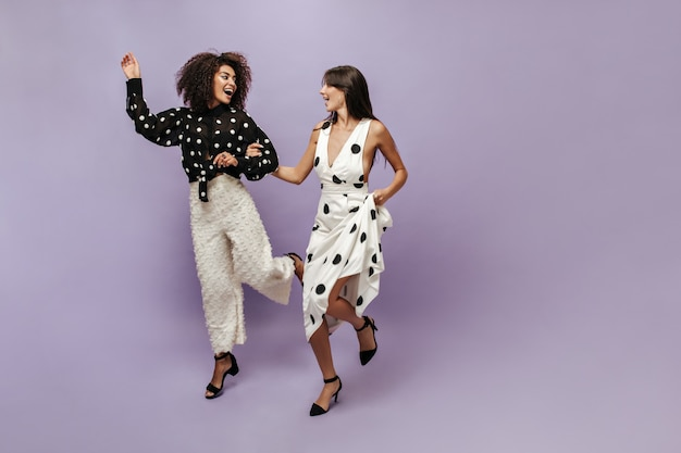 Krullend stijlvol meisje in zwarte blouse met lange mouwen en witte wijde broek die lacht en naar haar vriend kijkt in lichte moderne jurk