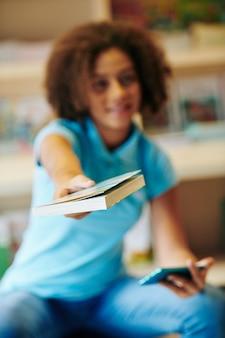Krullend tienermeisje uitgestrekte handen met boek naar camera, selectieve aandacht