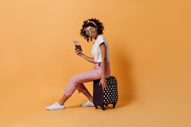 Krullend vrouwelijke reiziger zittend op koffer