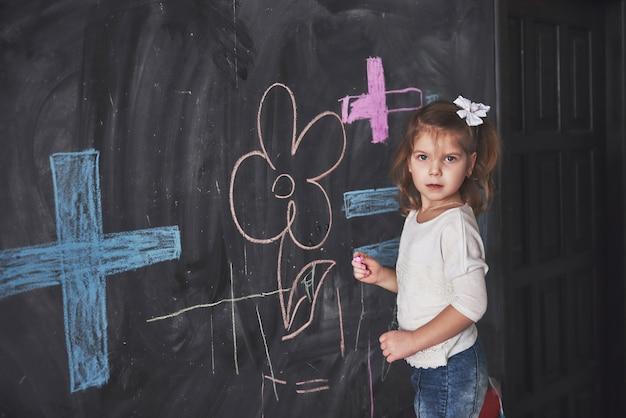 Krullend weinig babymeisje dat met kleurpotloodkleur op de muur trekt. werk van kind. leuke leerling die op bord schrijft