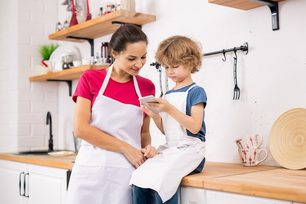 Krullende blonde jongen in schort die zijn moederrecept in smartphone toont terwijl hij het allebei in de keuken bespreekt