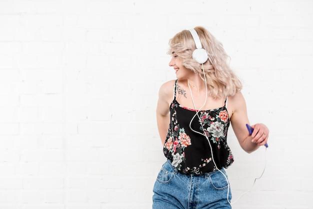 Krullende blondevrouw in hoofdtelefoons die aan muziek en het dansen luisteren