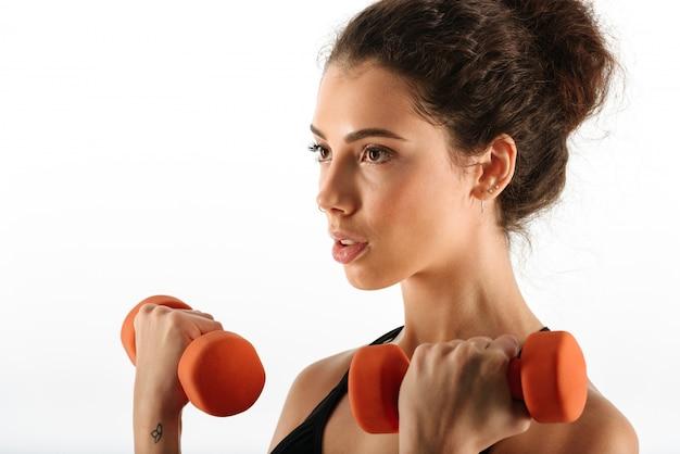 Krullende brunette fitness vrouw doet oefening met halters