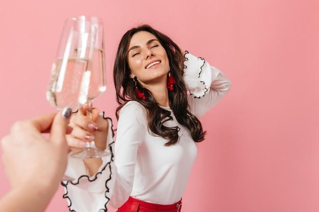 Krullende dame die van gerinkel van wijnglazen geniet. portret van meisje lachend met gesloten ogen op roze achtergrond.
