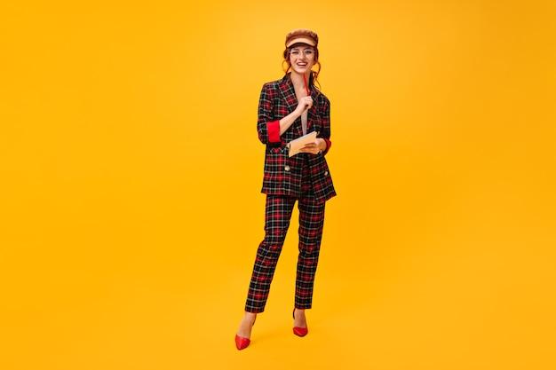 Krullende dame in geruite outfit houdt notitieboekje en rood potlood vast