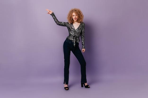 Krullende dame in glanzende blouse en spijkerbroek disco dansen op paarse geïsoleerde ruimte.