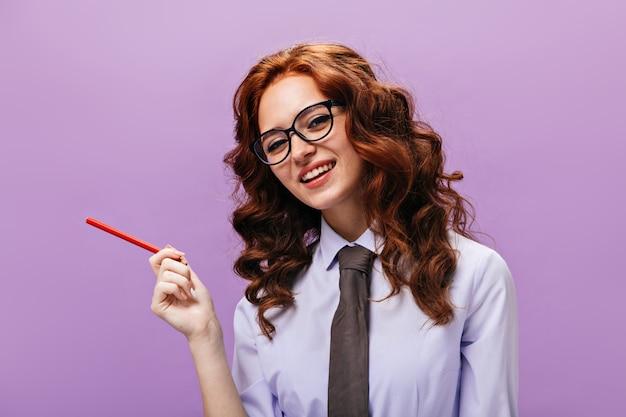 Krullende dame in shirt en bril houdt rood potlood vast