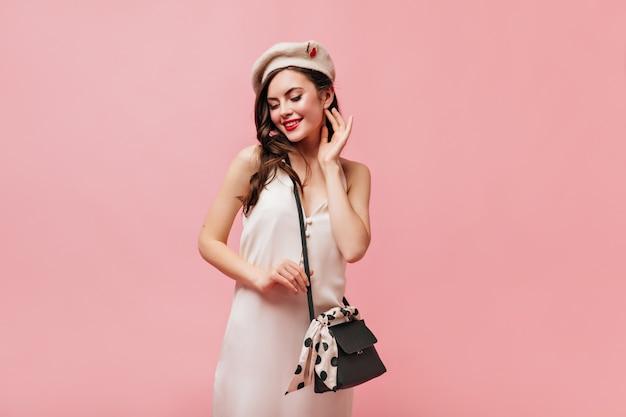 Krullende dame met rode lippenstift keek bedeesd naar beneden. vrouw in witte zomerjurk en baret houdt zwarte tas.