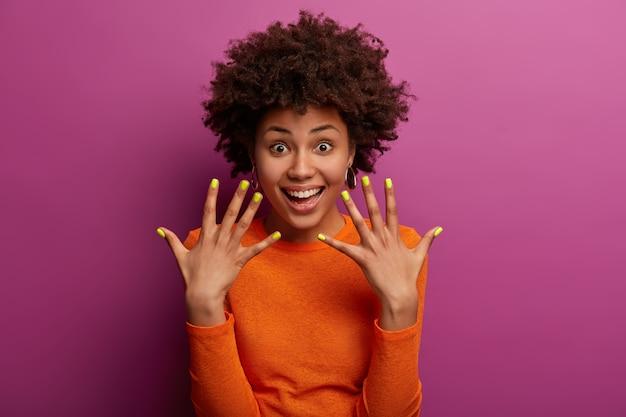 Krullende etnische vrouw toont gemanicuurde gele nagels, heeft een blije uitdrukking, lacht blij, blij na een bezoek aan de manicure, draagt een casual oranje trui, geïsoleerd over paarse muur, houdt de handen omhoog