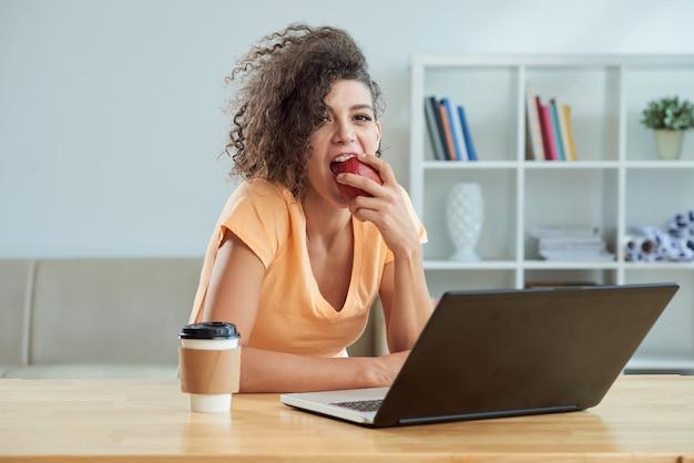 Krullende jonge cauasian-vrouw die appel voor laptop thuis eet