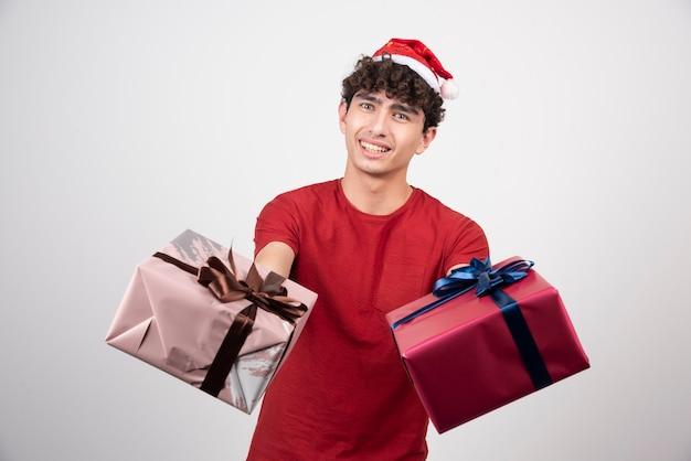 Krullende jonge man die geschenkdozen weggeeft.