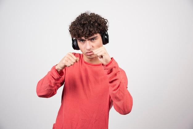 Krullende jonge man luisteren naar lied en ponsen.