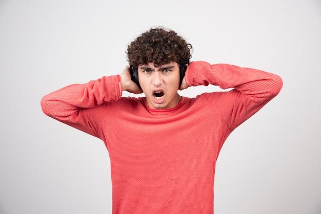 Krullende jonge man luisteren naar lied en schreeuwen.