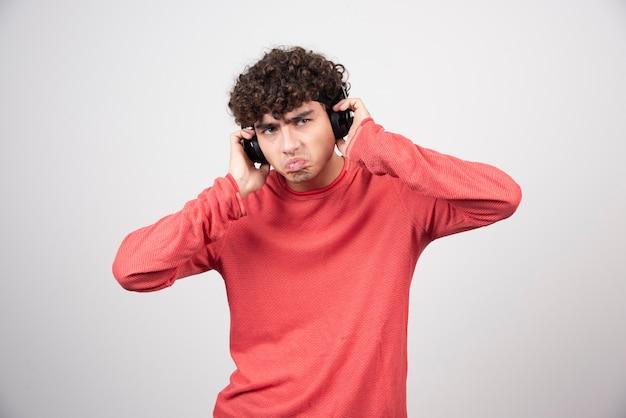 Krullende jonge man met koptelefoon luisteren lied met verveelde uitdrukking.