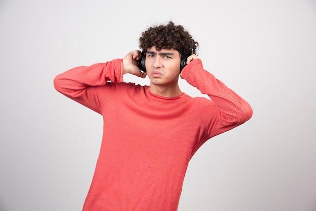 Krullende jonge man met koptelefoon luisteren naar lied.