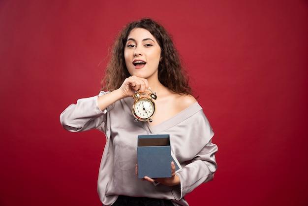 Krullende jonge vrouw die klok uit giftdoos neemt.