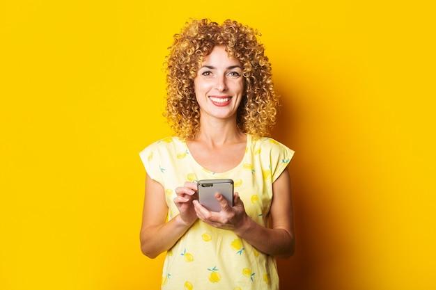 Krullende jonge vrouw die lacht houdt een telefoon op een gele achtergrond.
