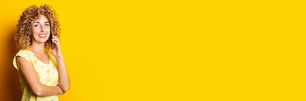 Krullende jonge vrouw die lacht praten aan de telefoon op een gele achtergrond. banier. Premium Foto