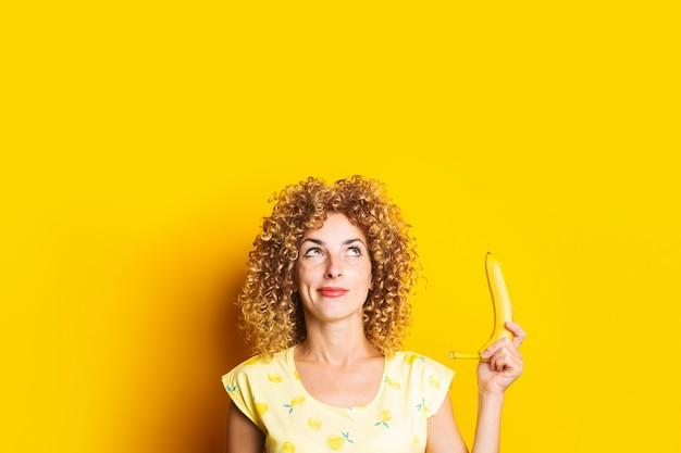 Krullende jonge vrouw die peinzend een banaan houdt die omhoog op een gele achtergrond kijkt.