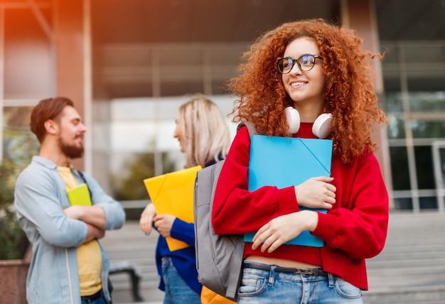 Krullende jonge vrouw en studentenvrienden tijdens toelating tot de universiteit