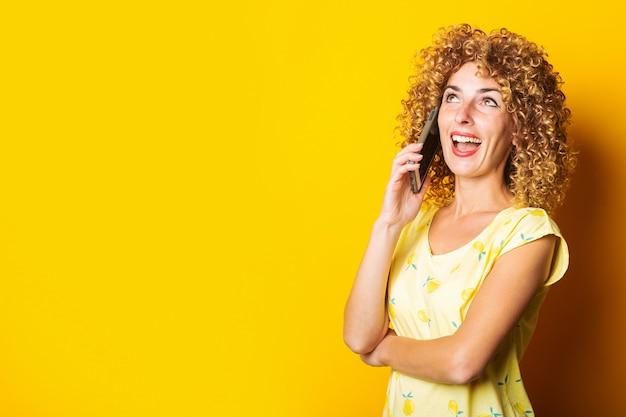 Krullende jonge vrouw praten aan de telefoon op een gele achtergrond.