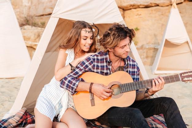 Krullende jongeman die gitaar speelt voor zijn vriendin die bij de campingtent zit