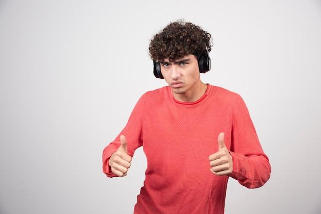 Krullende jongeman die naar een lied luistert en duimen opgeeft.