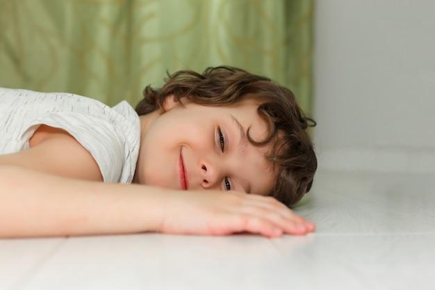 Krullende jongen die thuis op witte vloer ligt en glimlacht. het concept van vloerverwarming, kwaliteitslaminaat.