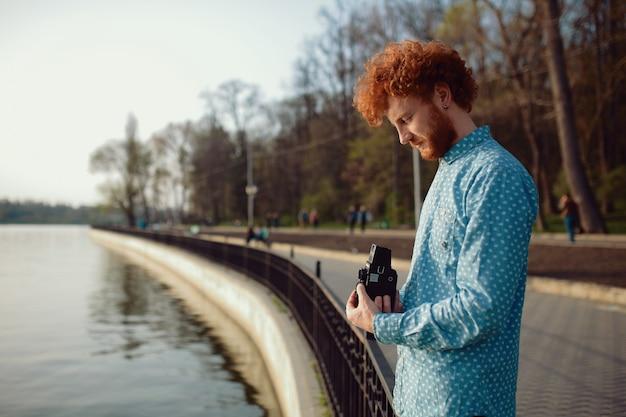 Krullende kerel die foto's van het meer maakt op een filmcamera van gemiddeld formaat