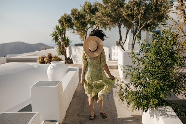 Krullende kortharige vrouw in gebloemde jurk en schipper rent naar buiten