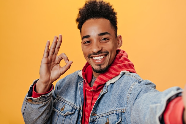 Krullende man in spijkerjasje toont ok teken en neemt selfie